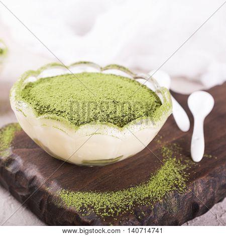 Tiramisu cake with green matcha tea in glass bowl on wooden cutting board.