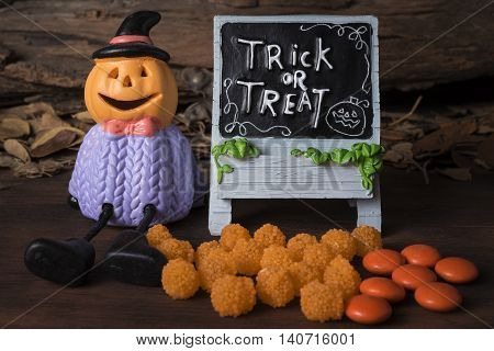 Halloween pumpkin head jack o lantern with trick or treat board and orange candy on wooden background