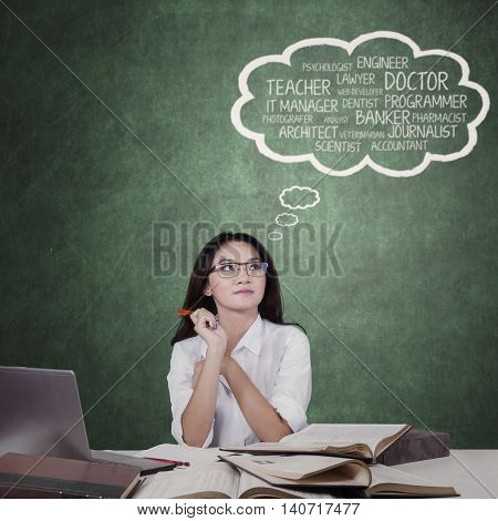 Portrait of a teenage schoolgirl studying in the class while thinking dream jobs
