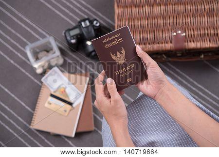 women hand holding Thailand travel passport with camera money budget on bag travel. tourism concept.