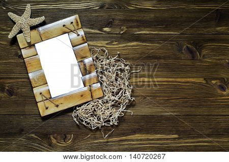 Bamboo frame with starfish on wooden background.