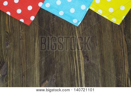 Colorful polka dot napkins on wooden background. Background from multi-colored textile napkins with polka dots. Red sky blue and yellow napkins.