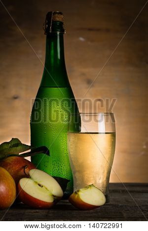 Apple cider in glass bottle with water drops, copy space