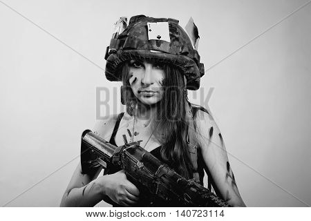 Pretty young girl in helmet with ak-104 over white background