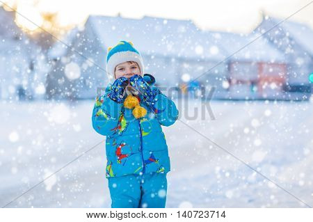 Cute little kid boy in colorful winter clothes having fun, outdoors during snowfall. Active outdoors leisure with children in winter. Happy child