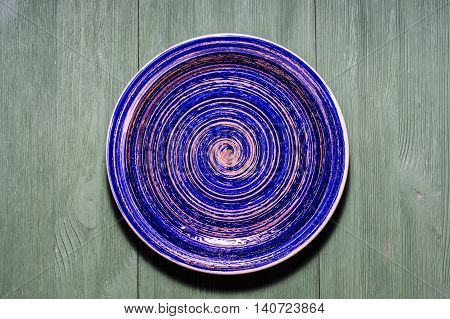 Blue pottery glazed plate. Ceramic plate on wooden background. Flat lay composition.