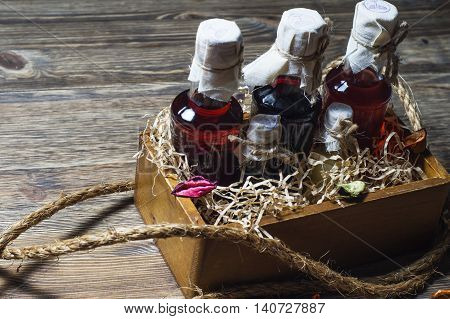 Small bottles of liquor in a wooden box on a wooden background. Small bottle with alcohol.