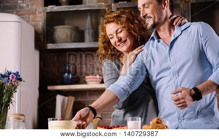 Lets try it. Smiling handsome man taking a jar from the table while his wife standing behind him with hands on his shoulders