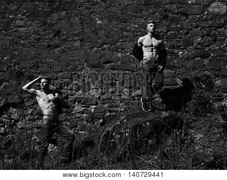 Young men twins with sexy body show their muscular bare torso and abs outside black and white on mural background
