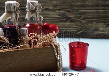 Bottles of liquor in a wooden box decorated with straw pearl beads and red ceramic hearts on a wooden background.
