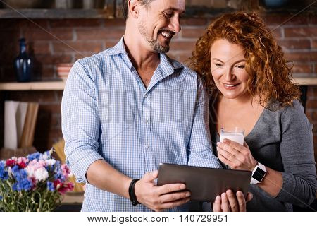 So interesting. Soigne surprised woman looking with interest at the tablet in hands of a satisfied man while being in the kitchen