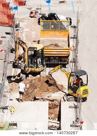 Udine , Italy - June 28 2016 : Men at work with excavator to do the excavation for the laying of drains of a sewer.