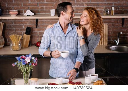 Have a nice day. Delighted man holding a cup of coffee and looking at his wife who embracing him in the kitchen