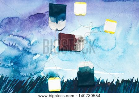 paper teabags lying on hand drawn watercolor picture blue color with spots