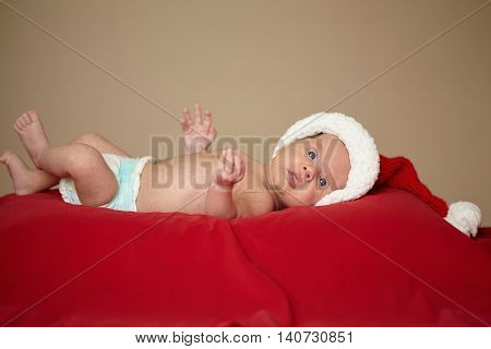 little cute baby with santa hat on red background
