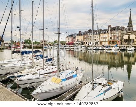 The moored yachts and medieval houses in old harbor. Honfleur, Normandy, France. Selective focus