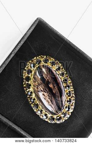 Agate golden brooch in black jewel box closeup