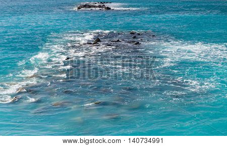 Waves rocks and stones on the open sea from above. Deep turquoise water