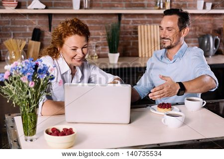 Look how cool it is. Smiling woman looking at the laptop while the man making a sign with a hand toward the screen