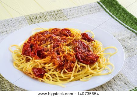 Spaghetti with tomato sauce on a white and green tablecloth. Pasta with sun-dried tomatoes on a yellow wooden background.