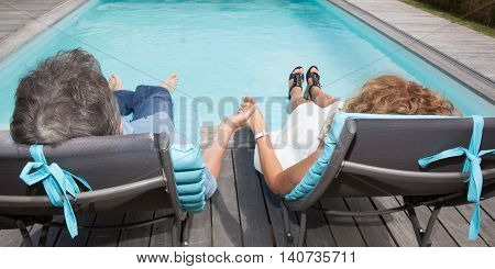 A happy couple on pool side chairs having fun