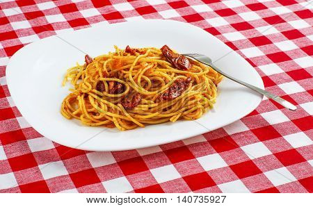 Spaghetti with tomato sauce on on red-white tablecloth. Pasta with sun-dried tomatoes.