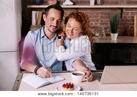 Time to be together. Charming woman sitting closely near her man and looking how he writing in the notebook