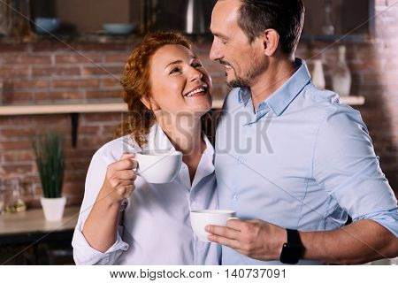 Unforgettable moment. Charming middle aged woman and a mature man looking at each other while holding cups of coffee