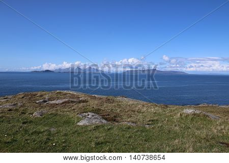 This is a view of Ardnamurchan Point and lighthouse, on the West Coast of Scotland. The picture was taken from a low hill, there is a stone cairn in the foreground, and Sanna Bay in the mid-distance. The sky is blue with white clouds.