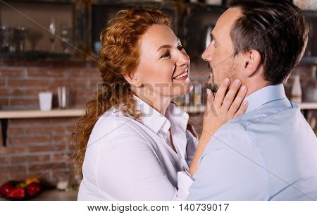 You have amazing eyes. Close up of beautiful middle aged woman looking at her man with tender and touching his face while being very closely to him in the kitchen