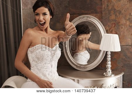 Happy bride showing thumb-up, smiling happy.