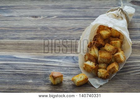 Cubes of bread croutons of white bread for cream soups in paper bag on a wooden background.