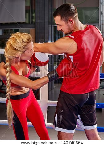 Couple Man and Woman Wearing Gloves Boxing in Ring. Boxing training at sport gym.