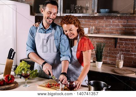 My support. Confident bearded man helping his wife cooking in the kitchen while she hugging him