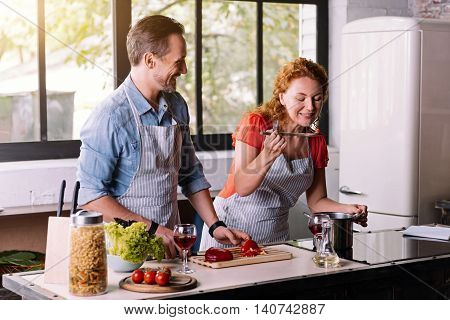We should try it. Contented woman tasting a dish while her husband standing near smiling and looking at her