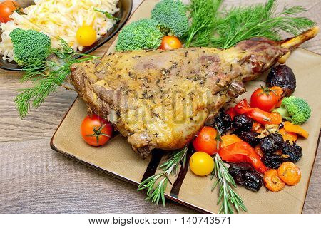 baked leg of lamb with vegetables and herbs on a plate on a wooden table. horizontal photo.