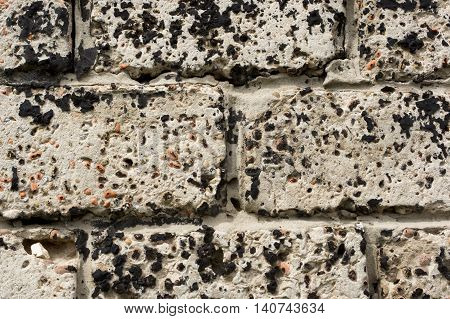 Wall made of concrete blocks stained black resin