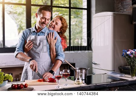 Cooking like a hobby. Satisfied middle aged woman hugging her handsome husband from the back while he cutting vegetables