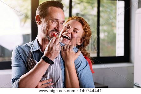 Never boring together. Charming woman laughing and cuddling her husband from the back while he eating a piece of paprika