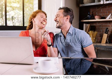 Eat it. Ecstatic man laughing at his wife eating a croissant while sitting at the table in the kitchen