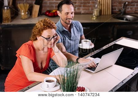 Do you like morning. Charming middle aged woman with glasses reading a news while her husband using a laptop in the kitchen