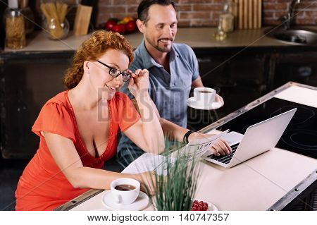Interesting information. Beautiful middle aged woman touching her glasses while reading a news and her husband using a laptop in the kitchen
