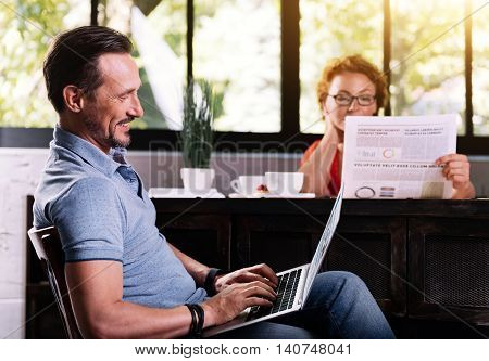 Dont forget to check your mail. Wistful mature bearded man sitting with the laptop while his wife reading a newspaper on the background