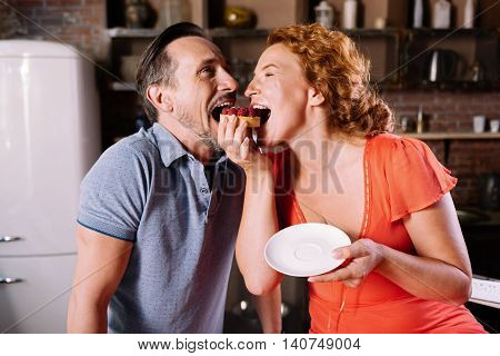 Hey look. Joyful middle aged couple biting both the same cake with berries
