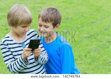 Children with smartphone. Boys looking to phone playing games or using application. Outdoor. Technology education leisure friendship people concept
