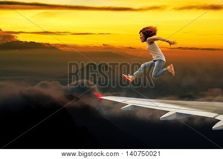 Mountain and morning light woman jumping on aircraft wing