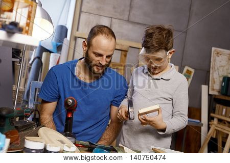 Father and son tinkering together in workshop.