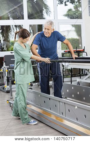 Physiotherapist Standing By Senior Patient Walking Between Paral