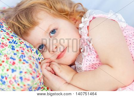 Little cute curly girl lies in a baby bed and a hand under her cheek. Face close up.