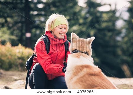 Smiling woman playing with akita inu dog on hiking forest trail. Recreation and healthy lifestyle outdoors autumn woods in mountains inspirational nature. Fitness trekking and activity concept.